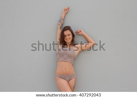 Beautiful woman in bikini with tattoos smiling for the camera against blank background with copyspace - stock photo