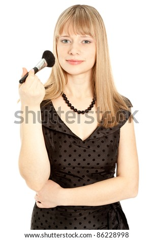 Beautiful woman in black dress holding a powder brush isolated on white - stock photo