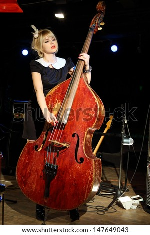 Beautiful woman in black dress plays wooden contrabass in night club. - stock photo