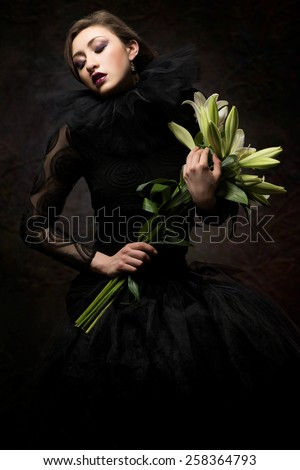 Beautiful woman in black lace dress with lilly flowers - stock photo
