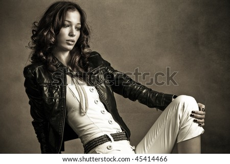 beautiful woman in black leather jacket, studio shot - stock photo