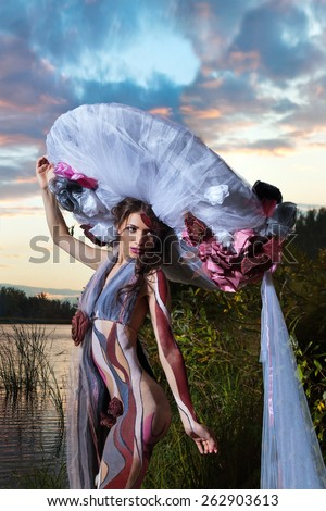 Beautiful woman in body-art on the river sunset  background - stock photo
