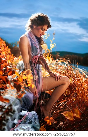 Beautiful woman in canes on the river sunset  background - stock photo