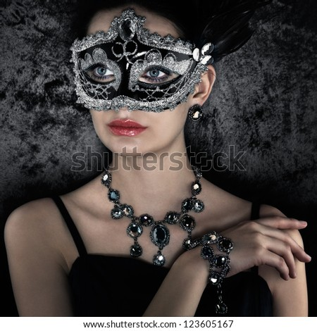 Beautiful woman in carnival mask on dark velvet background - stock photo