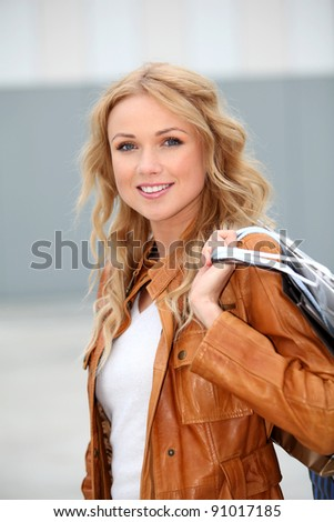 Beautiful woman in city holding shopping bags - stock photo