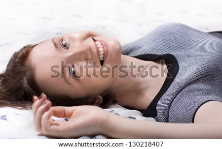 Beautiful woman in cloth lying on the bed close up - stock photo