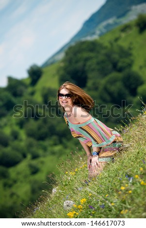 beautiful woman in dress sitting on the grass - stock photo