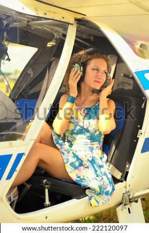 Beautiful woman in dress the pilot in a cockpit of the ultralight plane - stock photo