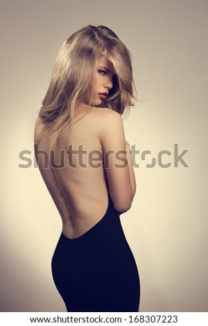 Beautiful woman in elegant evening black dress with naked rear. Portrait of young pretty caucasian blond female model with stylish hairdo wearing expensive fashionable dress.  - stock photo