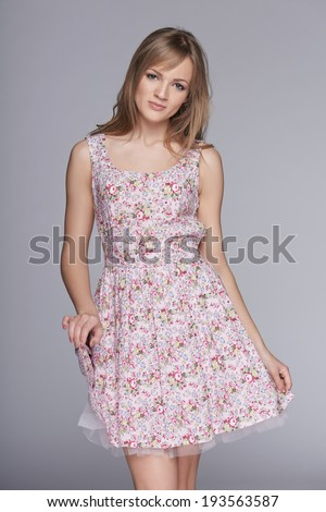 Beautiful woman in feminine floral sundress over gray - stock photo