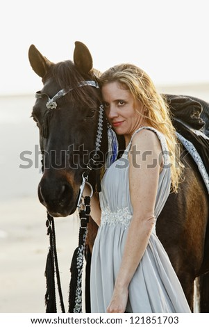 beautiful woman in formal dress standing with arabian horse - stock photo