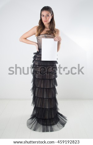 Beautiful Woman In Gorgeous Night Dress With Long Slicked Back Hair Showing A Blank White Paper Sign Whiteboard For Your Text Message Or Advertisement, Full-Length Studio Shot Over White Background - stock photo