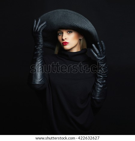 Beautiful woman in hat and leather gloves.fashion model girl trying black hat with large brim.halloween witch - stock photo