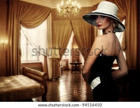 Beautiful woman in hat in luxury room. - stock photo