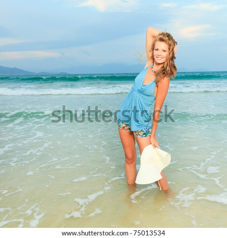 Beautiful woman in hat on the beach - stock photo