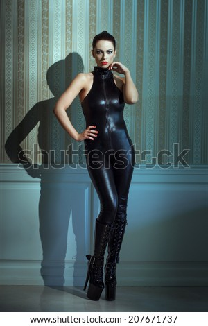 Beautiful woman in latex catsuit and high heel platform boots posing at vintage walls - stock photo