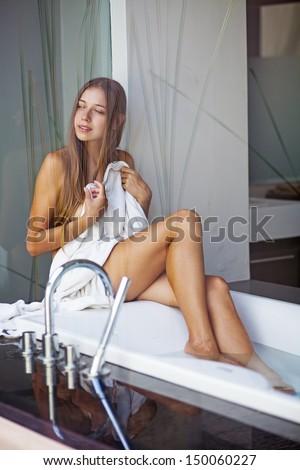 Beautiful woman in light interior of bathroom - stock photo