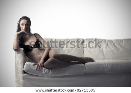 Beautiful woman in lingerie lying on a sofa - stock photo