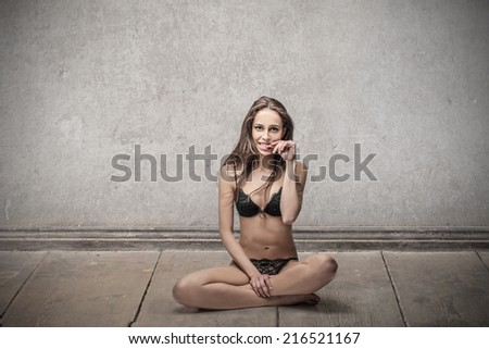 Beautiful woman in lingerie sitting on the floor posing for a picture - stock photo