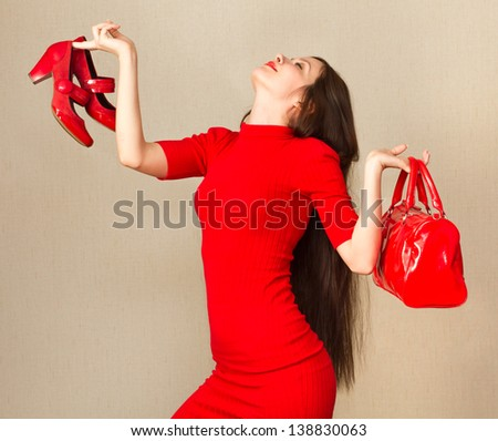 Beautiful woman in little red dress holding high heel shoes and handbag. - stock photo