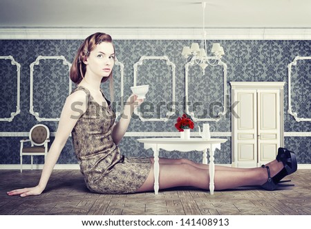 beautiful woman in little room drink a cup of tea (concept) - stock photo