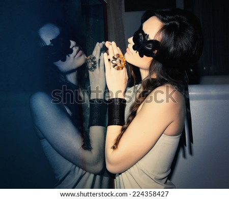 Beautiful woman in mask at mirror - stock photo