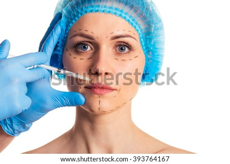 Beautiful woman in medical headwear is looking at camera, surgeon in medical gloves is making injection in face, isolated on white background - stock photo