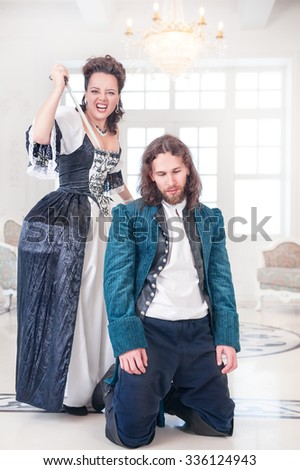 Beautiful woman in medieval dress killing man by dagger in the room - stock photo