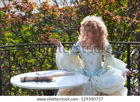 Beautiful woman in medieval dress with peacock feather in her hand, lacy mask and scroll on the table - stock photo