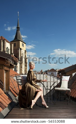 Beautiful woman in negligee with glass of champagne on the roof terrace - stock photo