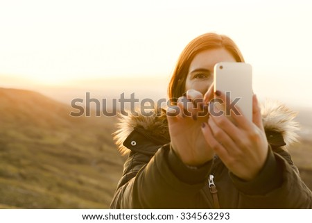 Beautiful woman in outdoor making a selfie - stock photo