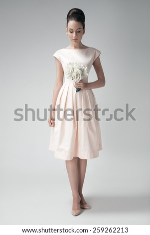 Beautiful woman in pink retro dress. White roses in hand. Gray background. - stock photo