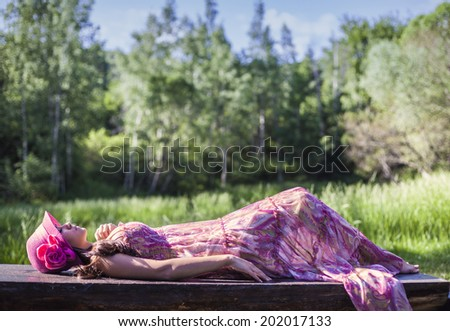 Beautiful woman in pink, sleeping in the summer forest - stock photo