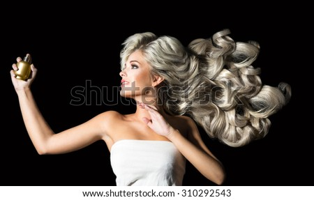 Beautiful  woman in profile with perfume on the black background - stock photo