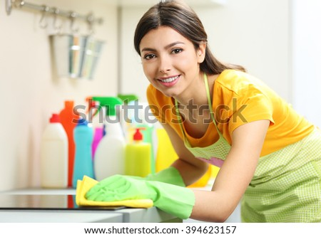 Beautiful woman in protective gloves cleaning electric range with rag - stock photo