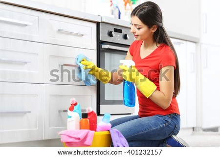 Beautiful woman in protective gloves cleaning kitchen cabinet - stock photo