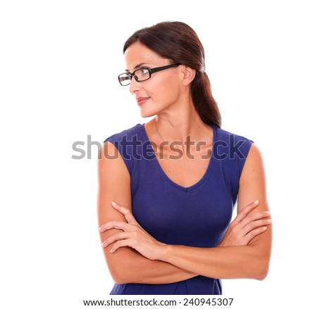 Beautiful woman in purple dress and spectacles looking to her right in white background - copyspace - stock photo