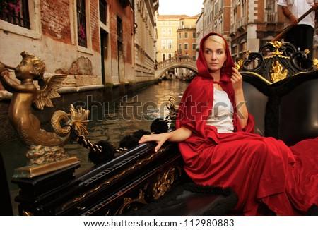 Beautiful woman in red cloak riding on gandola - stock photo