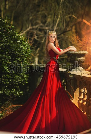 Beautiful woman in red dress and crown in the greens - stock photo