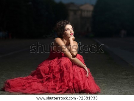 Beautiful woman in red dress at sunset - stock photo