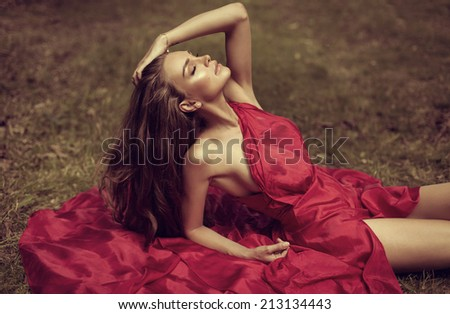 Beautiful woman in red dress lying on the grass - stock photo