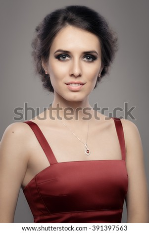 Beautiful Woman in Red Elegant Dress Wearing Ruby Jewelry - Portrait of a gorgeous girl with diamond jewellery and evening dress  - stock photo