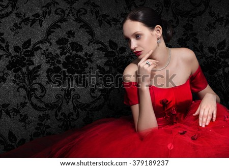 Beautiful woman in red evening dress on dark background. Space for text. - stock photo
