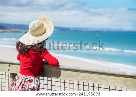 beautiful woman in red standing and looking to the sea  - stock photo
