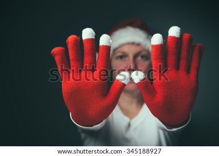 Beautiful woman in Santa Claus costume making Stop hand sign, retro toned image with selective focus - stock photo