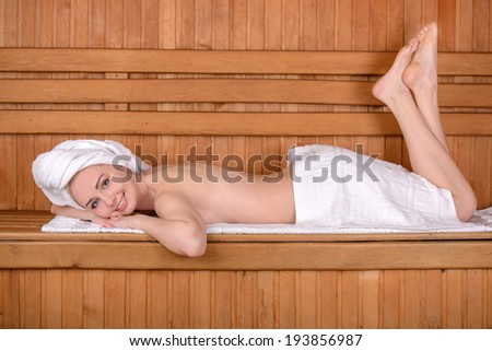 Beautiful woman in sauna. Attractive young woman wrapped in towel relaxing in sauna and smiling to you - stock photo