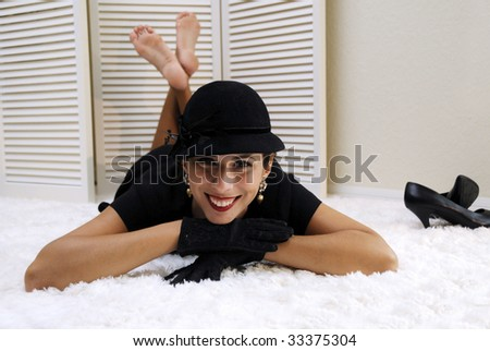 Beautiful woman in sequined black dress with black hat, gloves, laying on fluffy white rug - stock photo