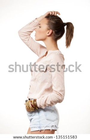 beautiful woman in shorts and shirt standing in profile to the camera - stock photo