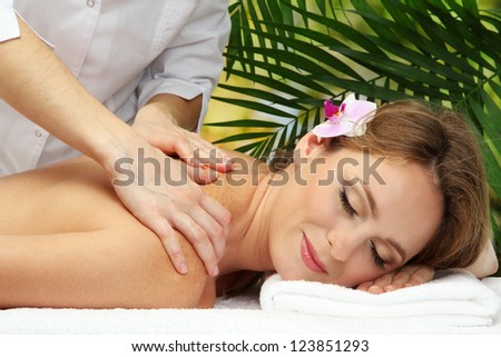 beautiful woman in spa salon  getting massage, on palm leaves background - stock photo