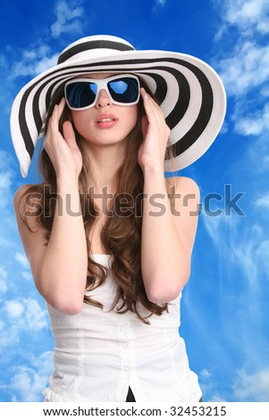 beautiful woman in striped hat and sunglasses with hands near face on background of the blue sky - stock photo